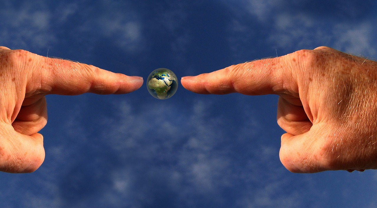 Fingers pointing at planet earth emphasising green values