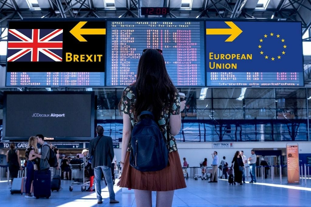 Woman looking at sign pointing to both EU and Brexit