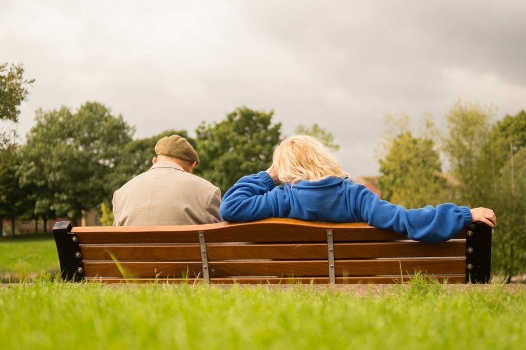 Retirees on a bench thinking of a care home